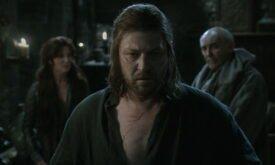 Лорд Эддард Старк в тяжелых раздумьях, за спиной его жена и мейстер Лювин