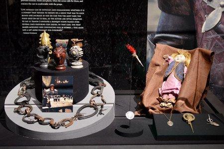 Все «экспонаты» подлинные — именно эти предметы использовались на съемках. Слева направо: цепь мейстера Лювина; фигурки с символами великих домов из лагеря Робба; дротик Якена Хгара, которым был убит Амори Лорх; подаренная Арье монетка Якена Хгара; кукла, которую Нед дарит Сансе.