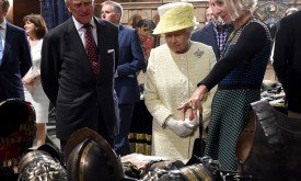 Создатель костюмов Мишель Клэптон рассказывает королеве и ее супругу принцу Филлипу о своей работе
