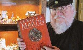 Джордж Мартин показывает обложку на фоне своей коллекции миниатюр