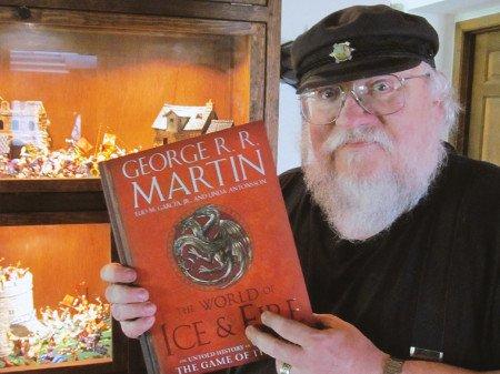 Джордж Мартин показывает обложку путеводителя на фоне своей коллекции миниатюрных рыцарей