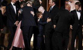 Команда Игры престолов обнимается на сцене; в центре — Динклейдж и сценарист Брайан Когман