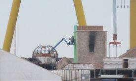 Одну из сторон обгоревшей башни закладывают зеленым экраном для спецэффектов (первая неделя июля)